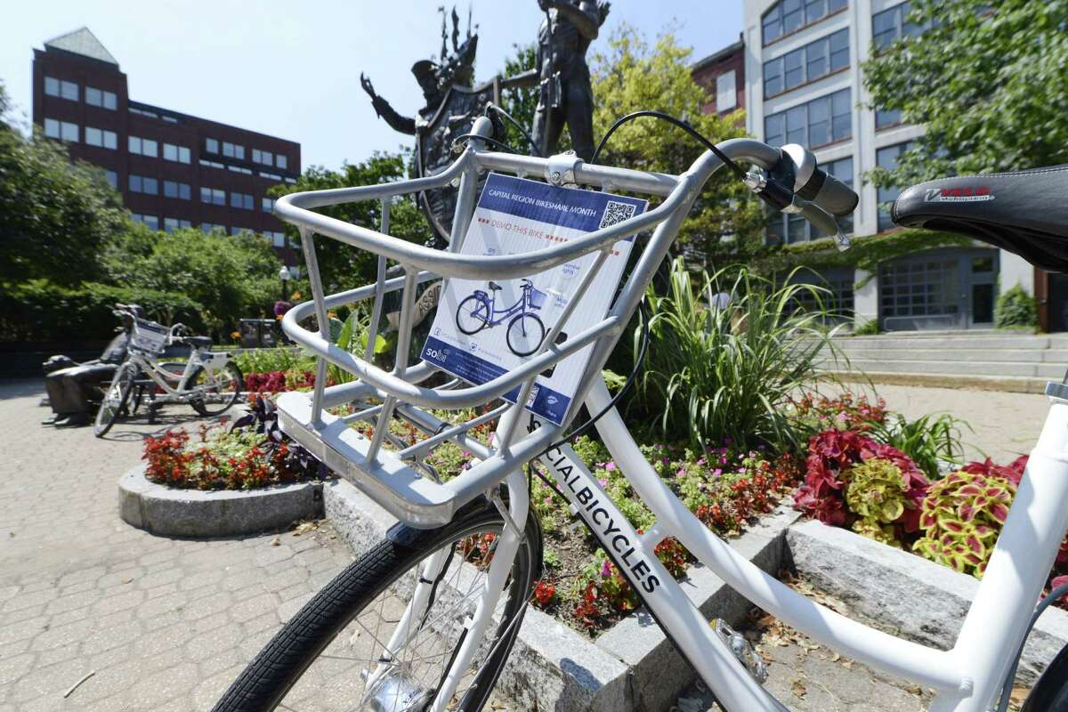 One of the bicycles available to share during Albany's BikeShare week is locked to a bench Monday, Aug. 11, 2014, at Tricentennial Square in Albany, N.Y. (Will Waldron/Times Union)