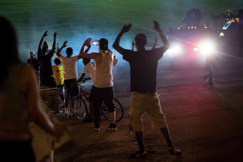 Protesters stand their ground as armored trucks make their way onto West Florissant Avenue in Ferguson, Mo., the night of Aug. 17, 2014. Missouri Gov. Jay Nixon announced early Monday that he would deploy the statea€™s National Guard to Ferguson, ratcheting up efforts to quell unrest that has paralyzed the city since an unarmed black teenager was killed by a white police officer. (Whitney Curtis The New York Times) ORG XMIT: XNYT10 Photo: WHITNEY CURTIS / NYTNS