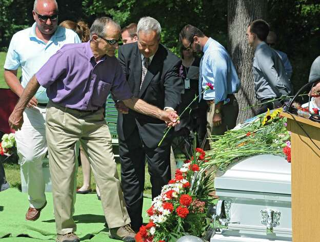 Arnold Talentino of Cortland, left, gets assistance from funeral director Tom Washock of Hans Funeral Home as he lays a flower in memory of his mother Hilda Talentino as family members, medical students and faculty from Albany Medical College attend a ceremony at Albany Rural Cemetery Monday, Aug. 18, 2014 in Menands, N.Y. The ceremony payed tribute to 335 people who died and donated their bodies to the Medical CollegeOs Anatomical Gift Program for medical education. (Lori Van Buren / Times Union) Photo: Lori Van Buren / 00028197A