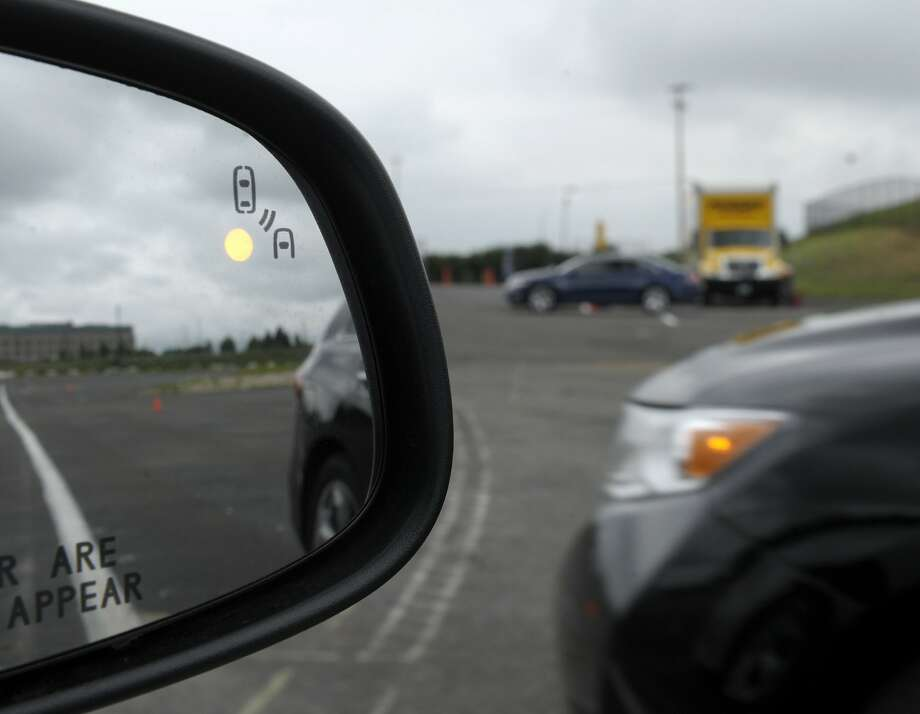 Automobile safety measures keep evolving, such as this side mirror warning in a Ford Taurus. Photo: Susan Walsh, Associated Press