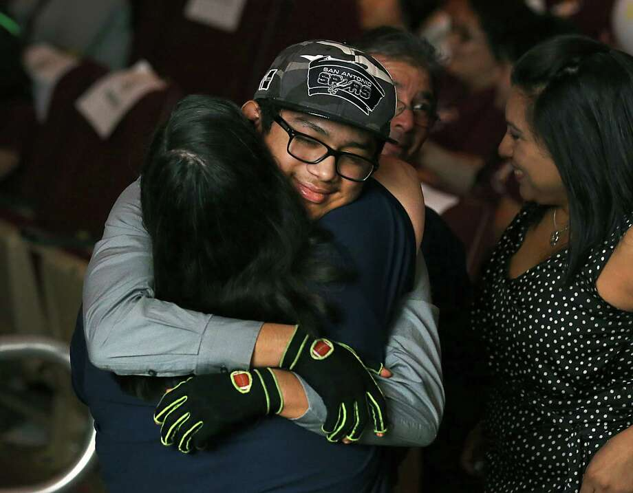 Jonathan Esquivel, 14, an Edgewood District student, is hugged by a former teacher after he was recognized for his heroic actions that saved the life of a teacher whom he pulled from a burning vehicle last year on a school trip.  The Edgewood Independent School District was celebrating it's annual pep rally for teachers and staff in the district's Fine Arts Theatre. Monday, Aug. 18, 2014. Photo: BOB OWEN, San Antonio Express-News / © 2012 San Antonio Express-News