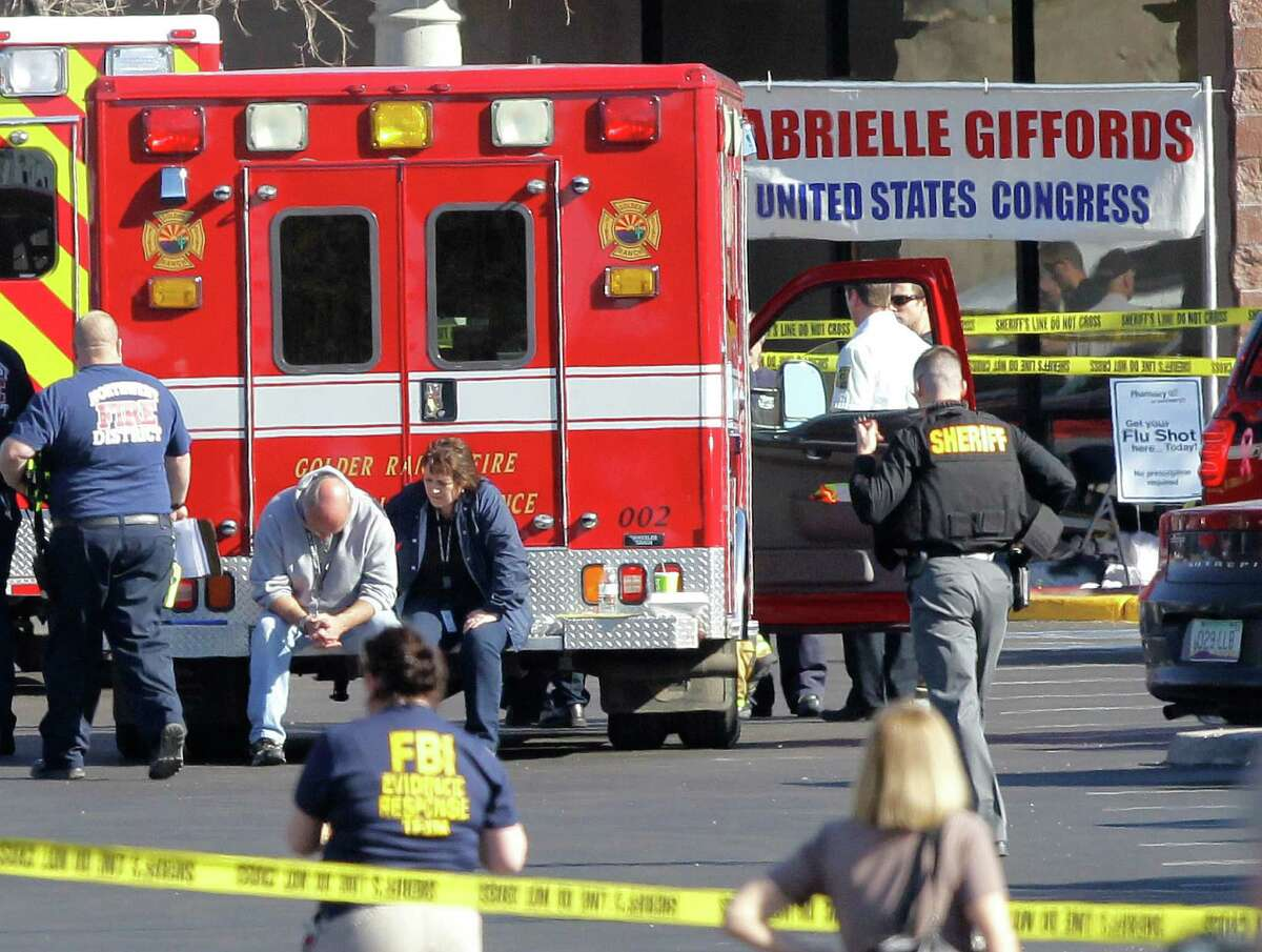Emergency personnel work at the scene where Rep. Gabrielle Giffords, D-Ariz., and others were shot outside a Safeway grocery store in Tucson, Ariz. on Saturday, Jan. 8, 2011.