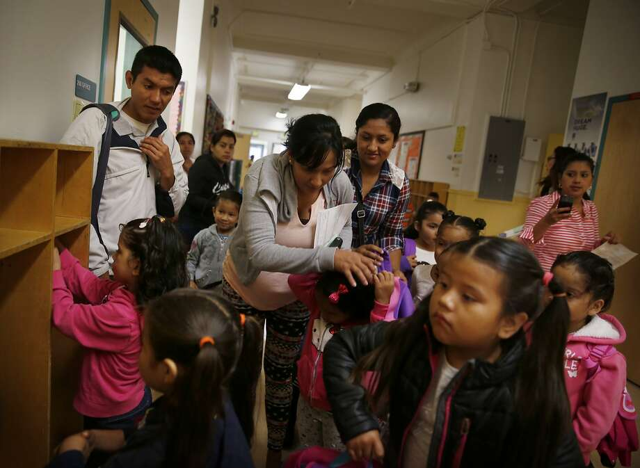 Parents help kindergarten students with their belongings as they prepare to head to the classroom on the first day of school at Mission Education Center Elementary School on Monday, August 18,  2014 in San Francisco, Calif. Photo: Lea Suzuki, The Chronicle