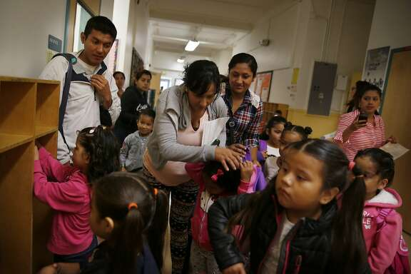 Parents help kindergarten students with their belongings as they prepare to head to the classroom on the first day of school at Mission Education Center Elementary School on Monday, August 18,  2014 in San Francisco, Calif.