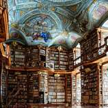 Carved-wood bookcases and a ceiling fresco dominate the Baroque library of the St. Florian Monastery, in Austria.