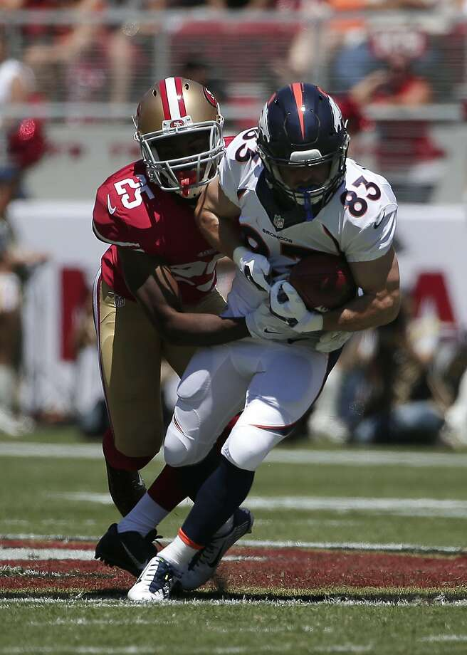 Rookie Jimmie Ward tackles Denver's Wes Welker after a first-quarter catch Sunday. Photo: Marcio Jose Sanchez, Associated Press