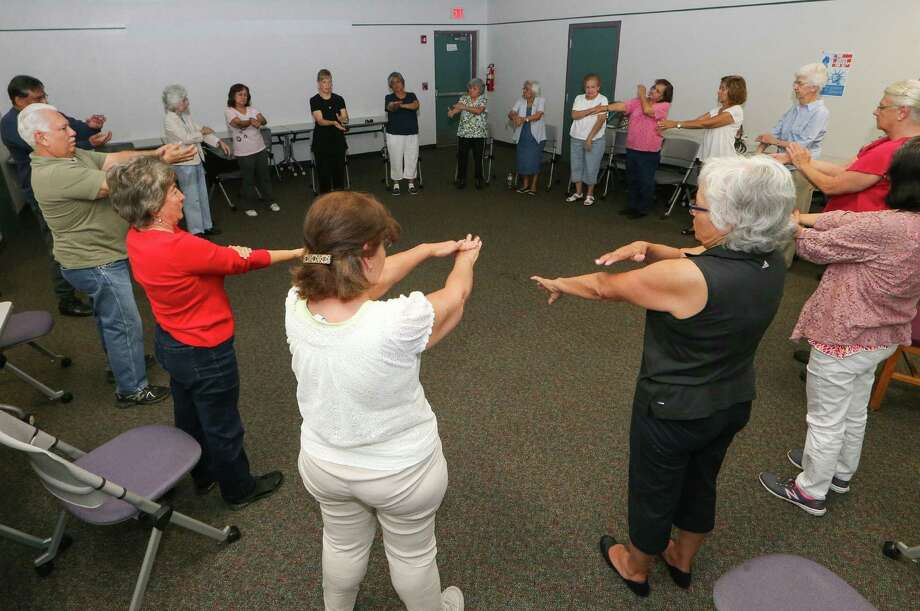 Mary Martha McNeel (top, fourth from left, in black top and black pants) leads a tai chi class at the Pan American Branch Library, 1122 W. Pyron Ave., last week. The sessions, which participants say help relieve stress and improve health, are held Fridays, 11 a.m.-noon. Photo: Marvin Pfeiffer / EN Communities / EN Communities 2014