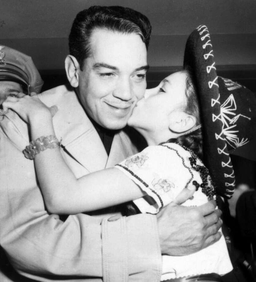 A little girl kisses Mario Moreno, famous for his role as Cantinflas, as he arrives at the San Antonio airport Oct. 15, 1957. Photo: Photos Courtesy UTSA Libraries Special Collections / UTSA LIBRARIES SPECIAL COLLECTIO