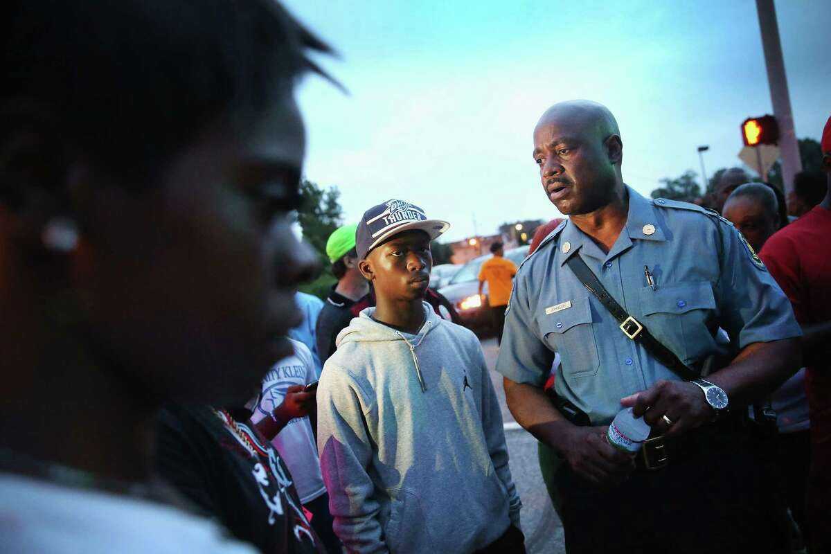 FERGUSON, MO - AUGUST 16: Capt. Ronald Johnson (R) of the Missouri State Highway Patrol, who was appointed by the governor to take control of security operations in the city of Ferguson, greets demonstrators on August 16, 2014 in Ferguson, Missouri. Violent protests have erupted nearly every night in the city since the shooting death of teenager Michael Brown by a Ferguson police officer on August 9. (Photo by Scott Olson/Getty Images)