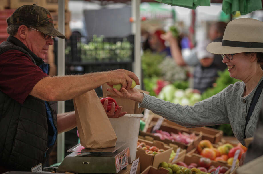 Bill Crepps, a vender for Everything Under the Sun, helps a customer at the Ferry Plaza Farmers Market in San Francisco on August 8th 2014. Photo: Sam Wolson, Contributor / Special To The Chronicle / ONLINE_YES