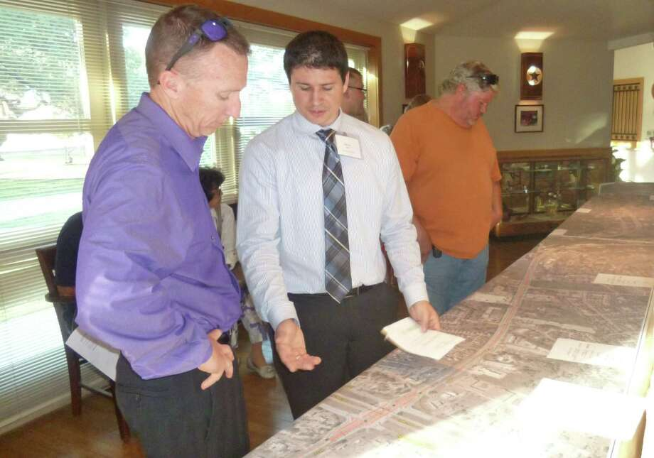 Helotes resident Steve Bodily (left), studies the new road design for FM 1560 at Texas 16 as Brian Allen, of Pape-Dawson Engineers, answers a question during a recent public meeting. Photo: Joni Simon / For The Northwest Light