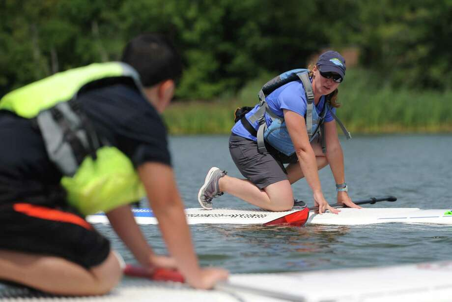 Class instructor Jennifer Brokaw demonstrates how to stand up on a paddleboard during the L.L. Bean Stand-Up Paddleboarding Discovery Course on Lake Kenosia in Danbury, Conn. Saturday, Aug. 16, 2014.  L.L. Bean offers discovery classes in paddleboarding and kayaking for first-timers, along with longer, more intensive introduction classes in both as well. Photo: Tyler Sizemore / The News-Times