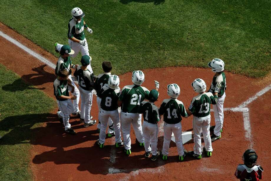 Pearland's Layne Roblyer, upper left, is greeted by teammates,  as Lynnwood catcher Robley Corsi III, bottom right, looks on, after hitting a three-run home run off Lynnwood pitcher Karsen Tjarneberg in the third inning of an elimination baseball game at the Little League World Series tournament in South Williamsport, Pa., Monday, Aug. 18, 2014. Pearland won 11-4. (AP Photo/Gene J. Puskar) Photo: Gene J. Puskar, Associated Press / AP