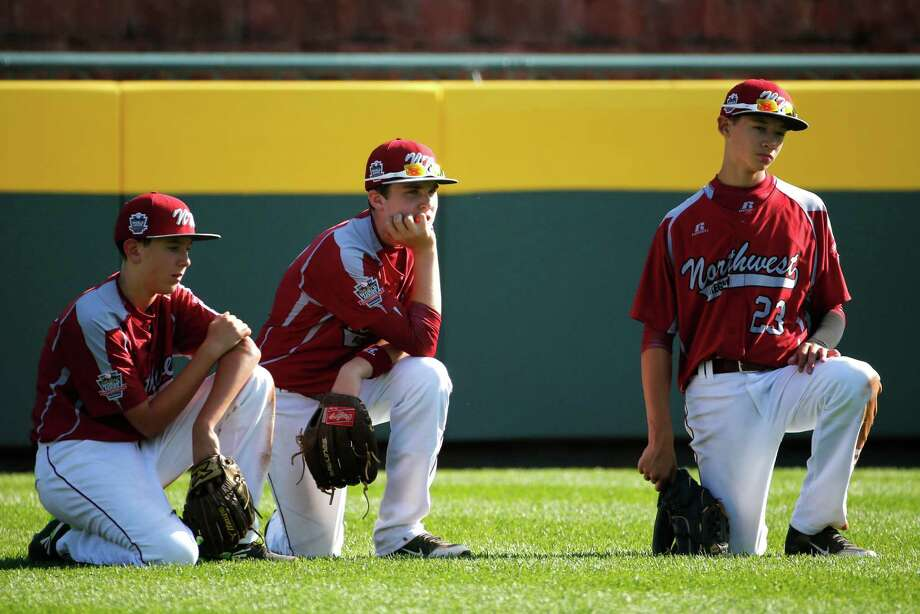 Lynnwood outfielders Karsen Tjarneberg, left, Ian Michael, center, and Colton Walsh (23) kneel in the outfield during a pitching change during the sixth inning of an elimination baseball game against Pearland at the Little League World Series tournament in South Williamsport, Pa., Monday, Aug. 18, 2014. Pearland won 11-4. (AP Photo/Gene J. Puskar) Photo: Gene J. Puskar, Associated Press / AP