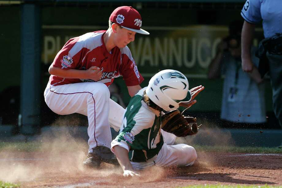 Pearland's Clayton Broeder (18) scores on a wild pitch by Lynnwood pitcher Tyler Durbin who covers home on the play during the sixth inning of an elimination baseball game against Lynnwood at the Little League World Series tournament in South Williamsport, Pa., Monday, Aug. 18, 2014. Pearland won 11-4. (AP Photo/Gene J. Puskar) Photo: Gene J. Puskar, Associated Press / AP