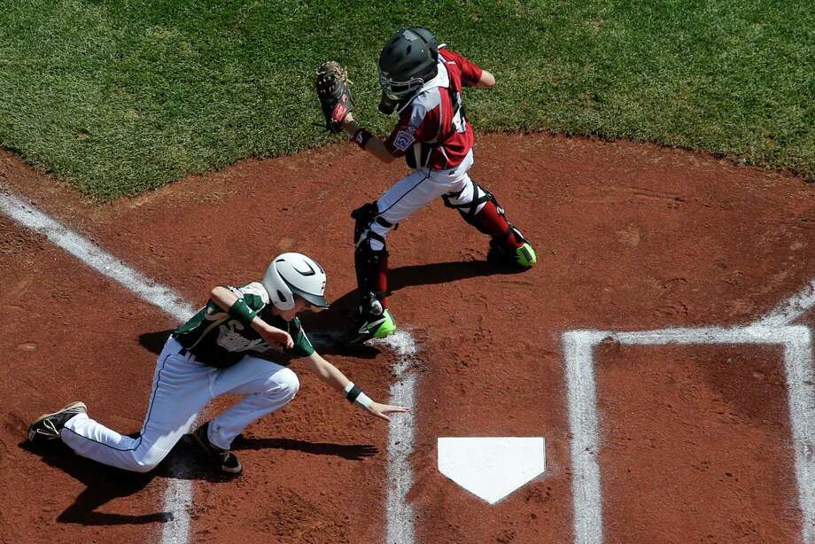 Pearland's Michael Groover, bottom, scores behind Lynnwood catcher Robley Corsi III on a single by Pearland's Matthew Adams off Lynnwood pitcher Logan Kruse during the first inning of an elimination baseball game against Lynnwood at the Little League World Series tournament in South Williamsport, Pa., Monday, Aug. 18, 2014. Pearland won 11-4. (AP Photo/Gene J. Puskar) Photo: Gene J. Puskar, Associated Press / AP