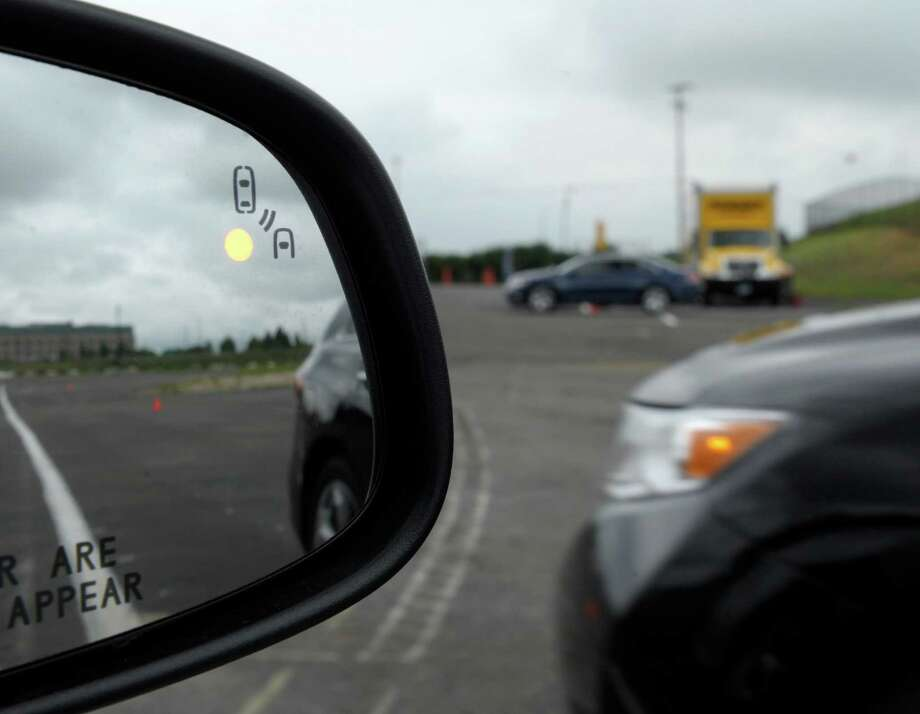 FILE - This May 22, 2012 file photo shows a demonstration of a side mirror warning signal in a Ford Taurus at an automobile testing area in Oxon Hill, Md. The Obama administration said Monday it is taking a first step toward requiring that future cars and light trucks be equipped with technology that enables them to warn each other of potential danger in time to avoid collisions. A research report released by the National Highway Traffic Safety Administration estimates that the technology could eventually prevent 592,000 left-turn and  intersection crashes a year, saving 1,083 lives. The agency said it will begin drafting rules to require the technology in new vehicles.  (AP Photo/Susan Walsh, File) ORG XMIT: WX102 Photo: Susan Walsh / AP