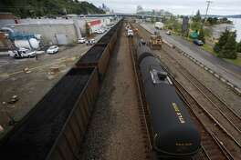 A coal train passes derailed tanker cars of an oil train beneath the Magnolia Bridge. Starved for markets, coal companies want to export their product to China. Development of terminals would send many long trains a day through Northwest population centers. Oregon rejected a proposed coal export terminal on Monday.