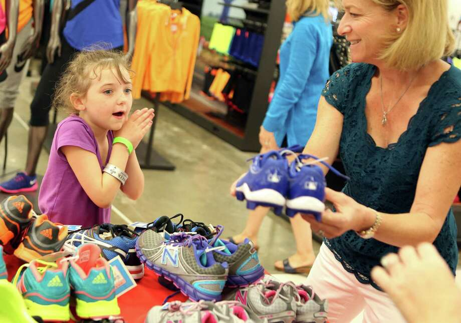 "Sara Cleveland, 7, is amazed by the shoes her volunteer shopper Nina Binstein found for her during the ""shoe party"" at Houston's Sports Authority on Post Oak Boulevard on Monday, Aug. 18, 2014, in Houston.  Photo: Mayra Beltran, Houston Chronicle / © 2014 Houston Chronicle"