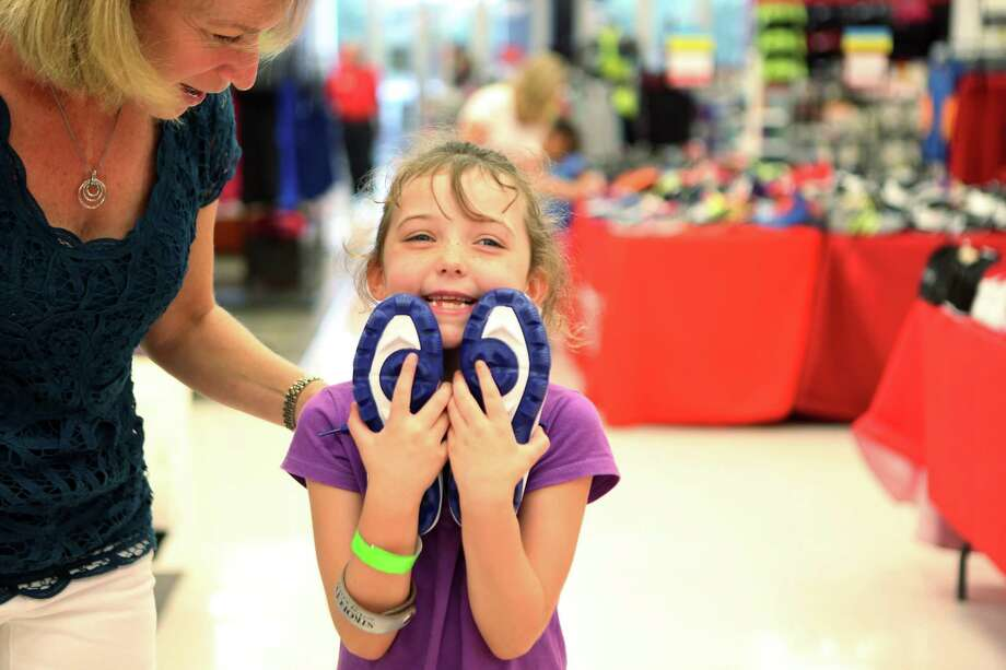 """I am so grateful,"" yells Sara Cleveland, 7, while walking with volunteer shopper Nina Binstein during the ""shoe party"" at Houston's Sports Authority on Post Oak Boulevard on Monday, Aug. 18, 2014, in Houston. Students were greeted by Trees of Hope Guild members and their families to help shop during the ""shoe party"" and provided food from Chick-fil-A. Photo: Mayra Beltran, Houston Chronicle / © 2014 Houston Chronicle"