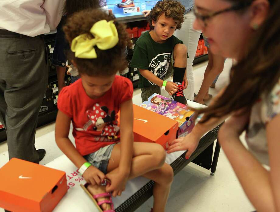 "Kayla Gunter, 5, and Fabian Sherk, 6, try on new shoes during the ""shoe party"" at Houston's Sports Authority on Post Oak Boulevard on Monday, Aug. 18, 2014, in Houston.  Photo: Mayra Beltran, Houston Chronicle / © 2014 Houston Chronicle"