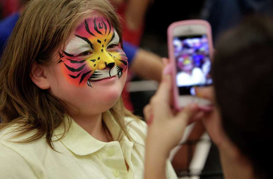 "Shyloh Matthews, 9, smiles for a photo after face painting  during the ""shoe party"" at Houston's Sports Authority on Post Oak Boulevard on Monday, Aug. 18, 2014, in Houston.  Photo: Mayra Beltran, Houston Chronicle / © 2014 Houston Chronicle"