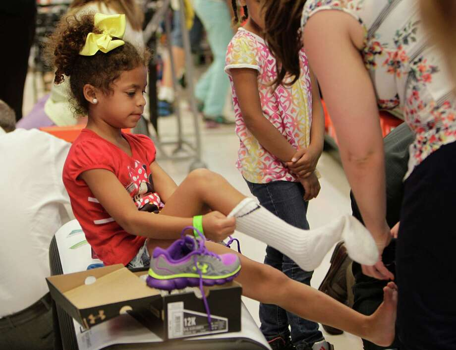 """Kayla Gunter, 5, tries on new shoes with her volunteer shopper during the """"shoe party"""" at Houston's Sports Authority on Post Oak Boulevard on Monday, Aug. 18, 2014, in Houston. Photo: Mayra Beltran, Houston Chronicle / © 2014 Houston Chronicle"""