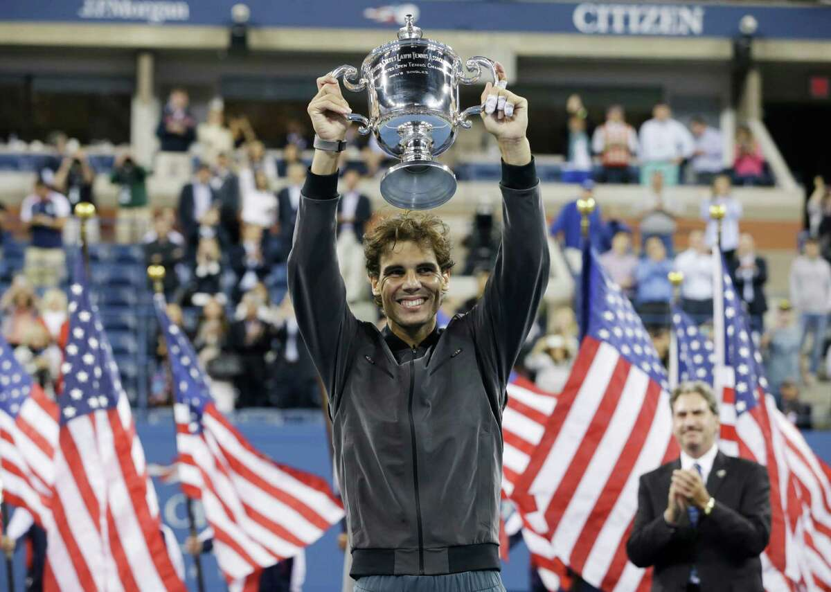 FILE - In this Sept. 9, 2013, file photo, Rafael Nadal, of Spain, holds up the championship trophy after winning the men's singles final over Novak Djokovic, of Serbia, at the 2013 U.S. Open tennis tournament in New York. Nadal will not defend his title at the U.S. Open because of an injured right wrist. Nadal and the tournament announced his withdrawal Monday, Aug. 18, 2014, a week before the year's last Grand Slam tournament begins. (AP Photo/Darron Cummings, File) ORG XMIT: NY151