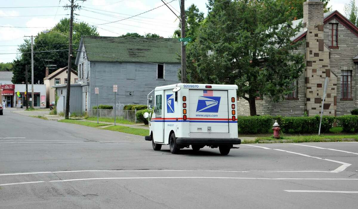 A US Postal vehicle drives west on 102nd St. crossing over 6th Ave., near the area of a recent shooting on Monday, Aug. 18, 2014, in Troy, N.Y. (Paul Buckowski / Times Union)