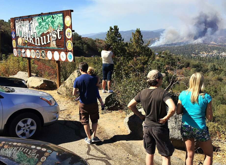 People watch a fire burning from the Highway 41 overlook on the way north into Oakhurst, Calif., Monday, Aug. 18, 2014. The fire is burning north of the community. (AP Photo/The Fresno Bee, Eric Paul Zamora) Photo: Eric Paul Zamora, Associated Press