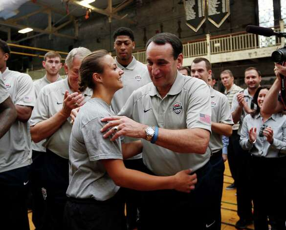 United States basketball head coach Mike Krzyzewski, right, hugs cadet Madaline Kenyon of Duanesburg, N.Y., after she ran an indoor obstacle course at the U.S. Military Academy on Monday, Aug. 18, 2014, in West Point, N.Y. Krzyzewski is a 1969 graduate of the academy. (AP Photo/Mike Groll) ORG XMIT: NYMG102 Photo: Mike Groll / AP