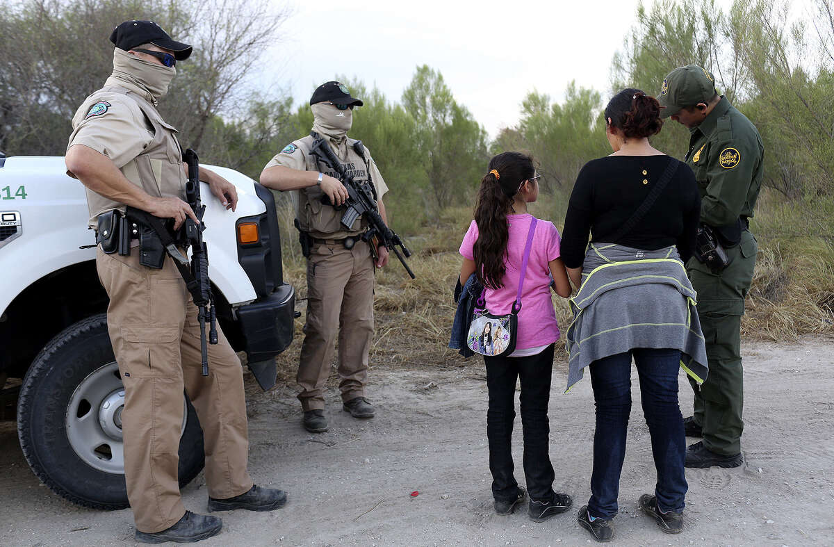 Central American immigrants are questioned by a U.S. Border Patrol agent, with Texas game wardens standing guard, after they crossed the Rio Grande by boat into the United States last Wednesday.
