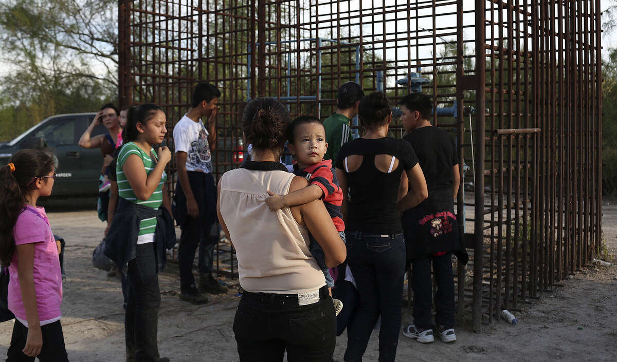 Maria Bertalina Ramirez of Honduras, holding her son, and other immigrants are guided to a clearing to be questioned.