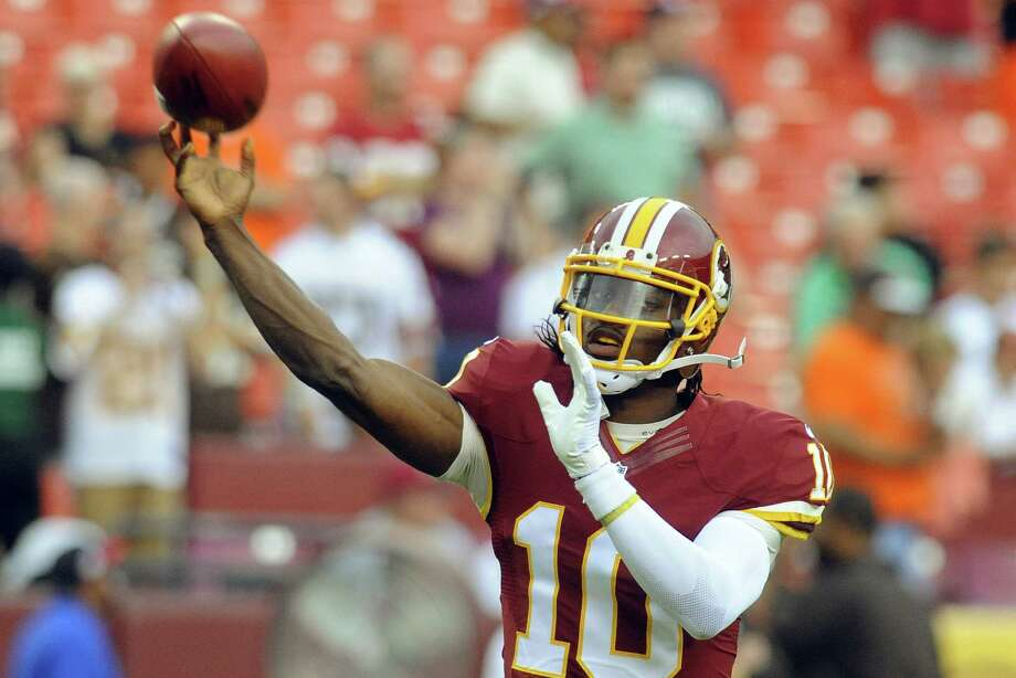 Washington Redskins quarterback Robert Griffin III throws during warm ups before an NFL preseason football game against the Cleveland Browns Monday, Aug. 18, 2014, in Landover, Md. (AP Photo/Richard Lipski) Photo: Richard Lipski, Associated Press / FR170623 AP