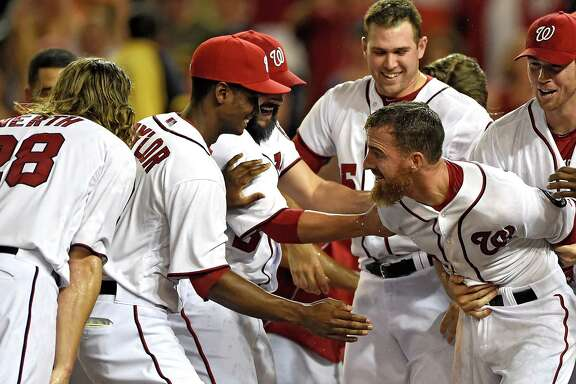Adam LaRoche, right, is mobbed by teammates after hitting a solo home run in the 11th inning to lift the Nationals to a 5-4 victory over the Diamondbacks, Washington's third consecutive walkoff win.