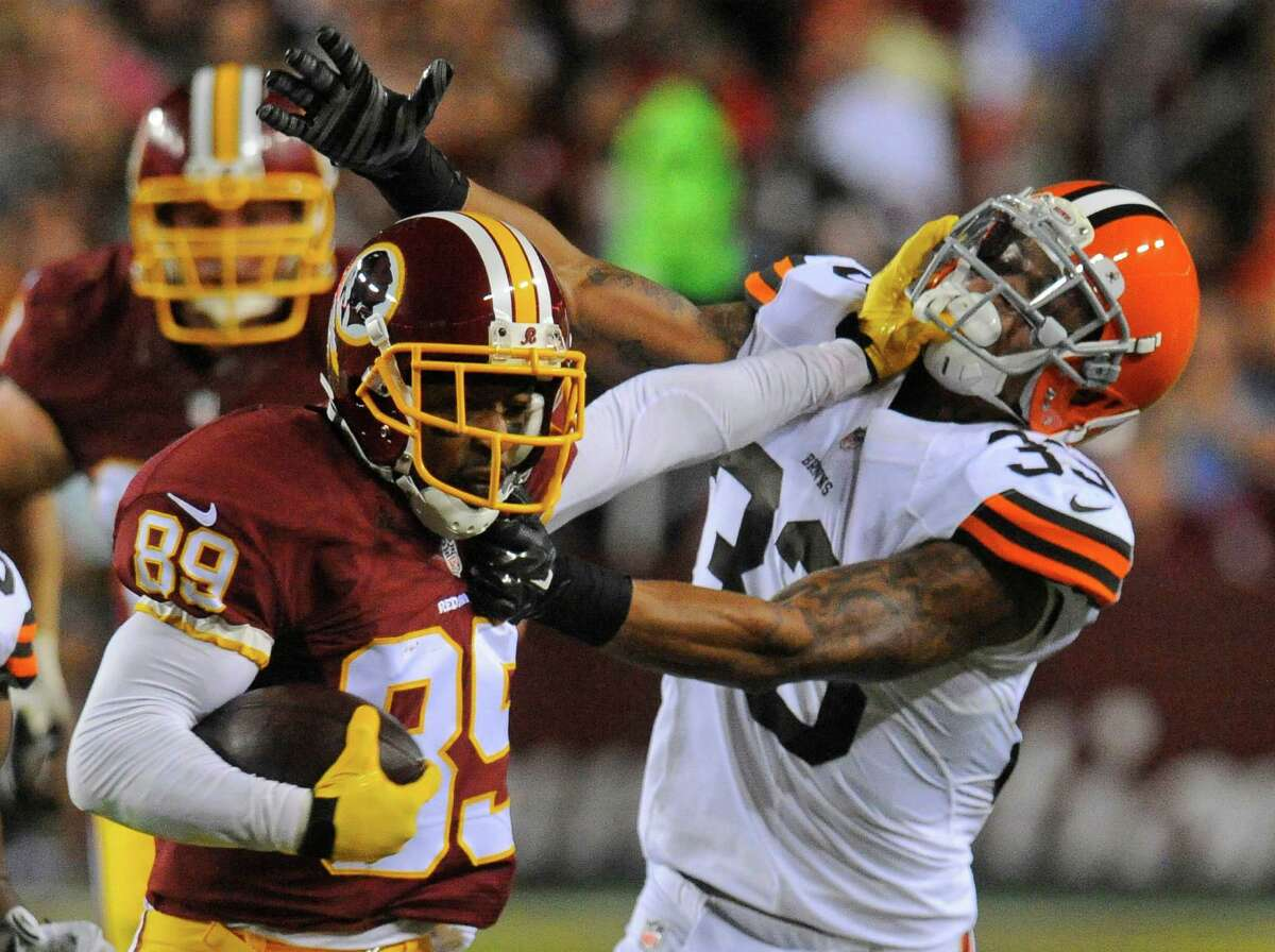 Washington Redskins wide receiver Santana Moss (89) stiff armsCleveland Browns cornerback Jordan Poyer (33) during the first half of an NFL preseason football game Monday, Aug. 18, 2014, in Landover, Md. (AP Photo/Richard Lipski) ORG XMIT: FDX120