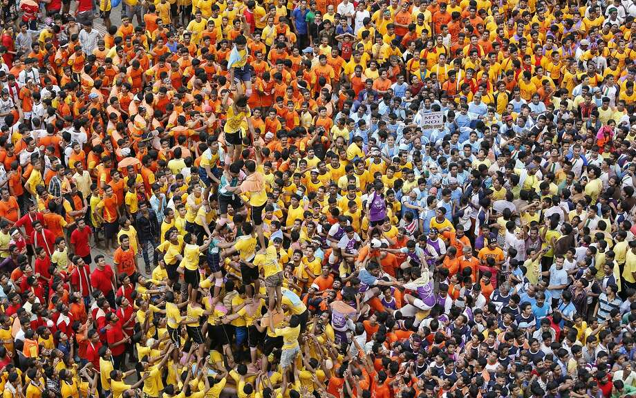"People watch as Indian youth form human pyramids to break the ""Dahi handi,"" an earthen pot filled with curd, an integral part of celebrations to mark Janmashtami in Mumbai, India, Monday, Aug. 18, 2014. Janmashtami is the festival that marks the birth of Hindu god Krishna. (AP Photo/Rajanish Kakade) Photo: Rajanish Kakade, Associated Press"