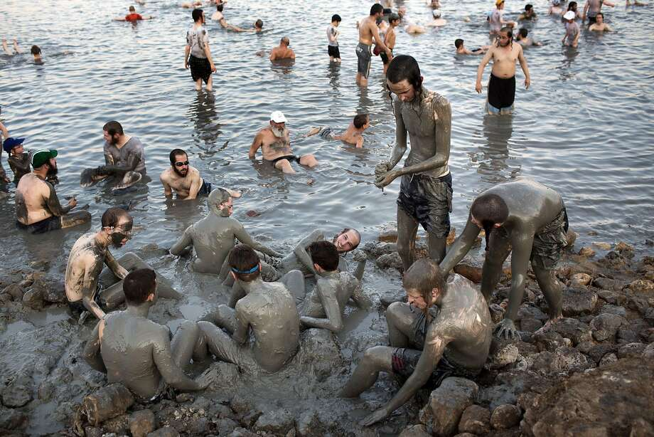 TOPSHOTS Ultra-Orthodox Jewish men and boys cover their bodies with mineral-rich mud, during their vacation, at a Men's only beach on the shores of the northern part of the Dead Sea on August 17, 2014, in the Israeli-occupied West Bank. AFP PHOTO/MENAHEM KAHANAMENAHEM KAHANA/AFP/Getty Images Photo: Menahem Kahana, AFP/Getty Images