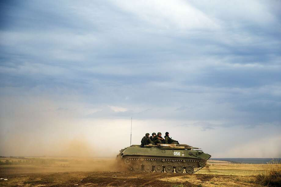 A Russian APC moves in a field in about 10 kilometers (6.2 miles) from the Russia-Ukrainian border control point at Russian town of Donetsk, Rostov-on-Don region, Monday, Aug. 18, 2014. (AP Photo/Pavel Golovkin) Photo: Pavel Golovkin, Associated Press