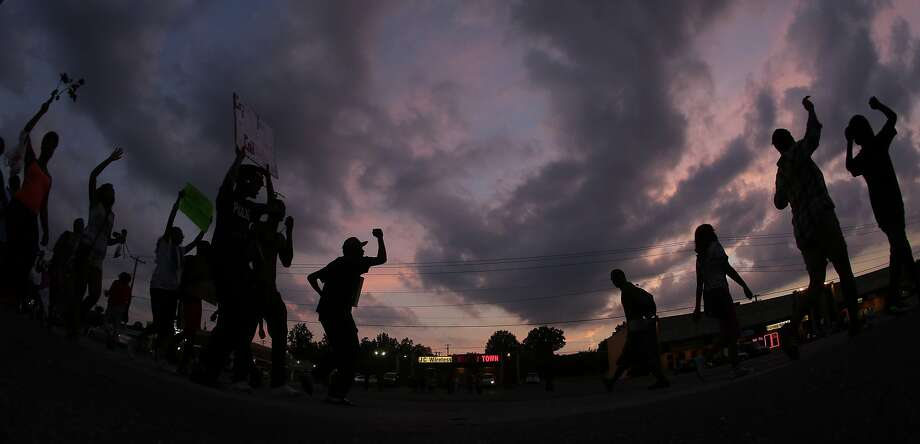 In this photo taken with a fisheye lens, people protest Monday, Aug. 18, 2014, for Michael Brown, who was killed by police Aug. 9 in Ferguson, Mo. Brown's shooting has sparked more than a week of protests, riots and looting in the St. Louis suburb. (AP Photo/Charlie Riedel) Photo: Charlie Riedel, Associated Press