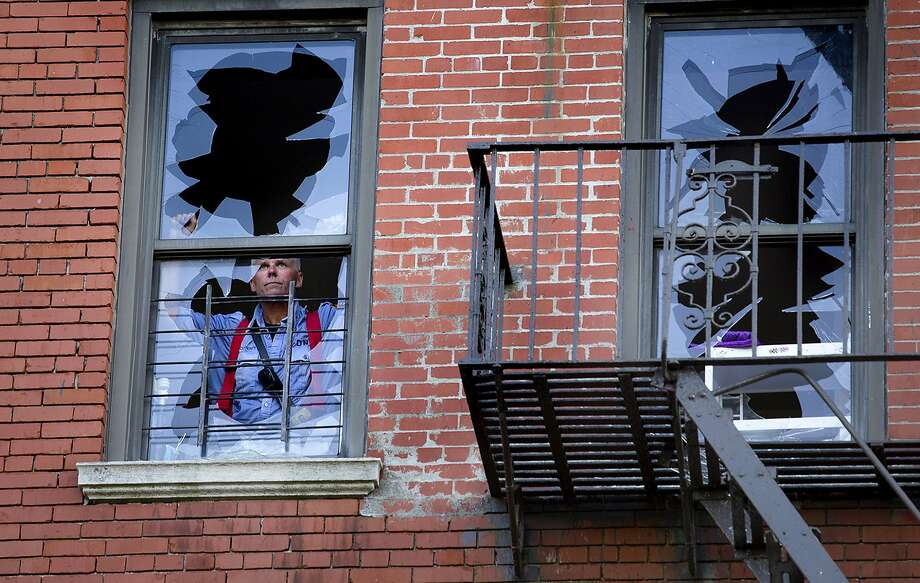 A member of the FDNY looks out a broken window at the scene of a multi alarm fire on West 136th Street in the Hamilton Heights neighborhood of New York, Monday, Aug. 18, 2014. Officials say the fire was on the second and third floors of the six-story building. (AP Photo/Craig Ruttle) Photo: Craig Ruttle, Associated Press