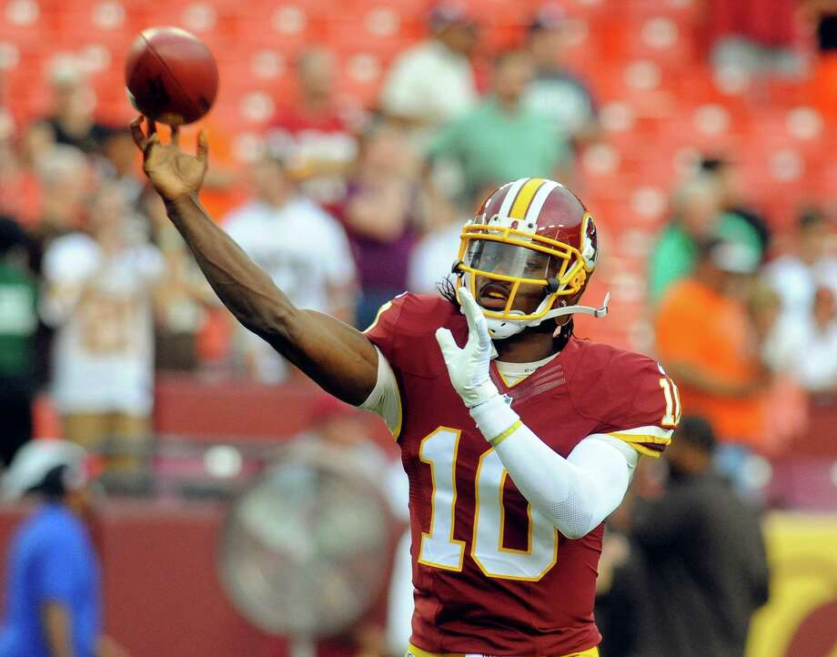 Washington Redskins quarterback Robert Griffin III throws during warm ups before an NFL preseason football game against the Cleveland Browns Monday, Aug. 18, 2014, in Landover, Md. (AP Photo/Richard Lipski) Photo: Associated Press / FR170623 AP