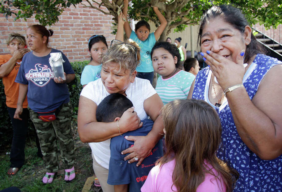Margarita Arroyo, center, of Pasadena and Lupe Lugo, right, comforts their grandchildren, as they watch firefighters battle a three alarm fire where Lupe and the children live at the Mar Del Sol Apartments, 9303 Woodfair, in Southwest Houston Tuesday, Aug. 12, 2014, in Houston. ( Melissa Phillip / Houston Chronicle ) Photo: Melissa Phillip, Houston Chronicle / © 2014  Houston Chronicle