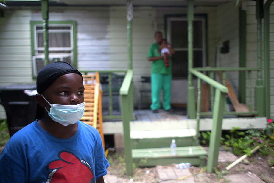 Daymon Thomas, 7, stands in his front yard where his grandmother, Peggy Thomas, was holding his 3-month-old sister Kiera Thomas before Daymon joined his parents and about 25 residents and members of the Texas Organizing Project to rally for more cleanup after recent chemical leakage from the now defunct Houston-based waste management company CES Environmental Services, where residents say chemicals spilled out onto the 4600 block of Kingsbury Street just south of Griggs Road near Calhoun Sunday, Aug. 10, 2014, in Houston. Daymon said he can smell the chemicals and he often rides his bike around the area where the leakage occurred. The company formally cleaned truck trailers, recycled oil and packaged waste for transport and disposal  Residents say they want the deserted plant cleaned up. Residents have complained about having trouble breathing and headaches from a continuous smell from the plant. ( Johnny Hanson / Houston Chronicle ) Photo: Johnny Hanson, Houston Chronicle / © 2014  Houston Chronicle