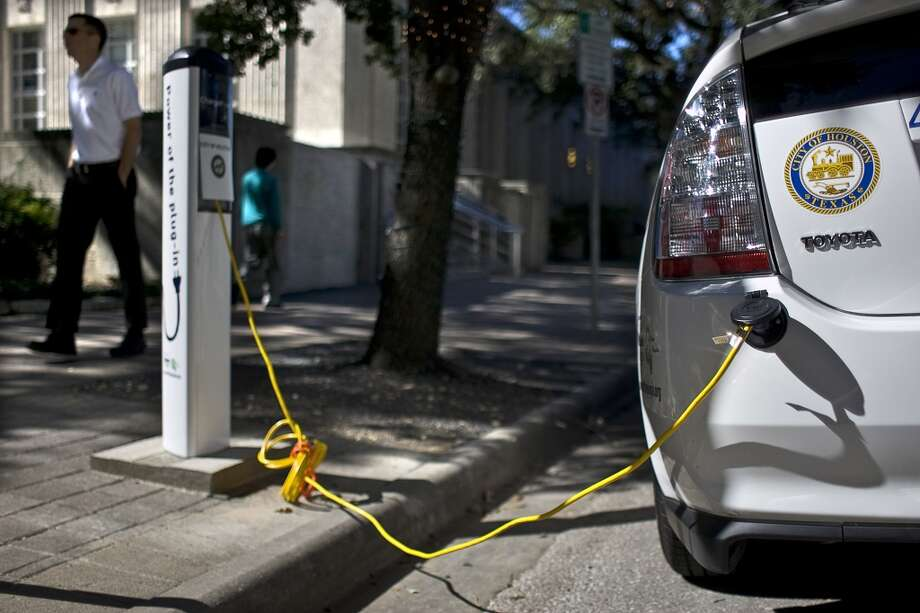 An electric car uses a charging station outside Houston City Hall in this file photo. For all the talk of transitioning to renewable energy, a PBPA speaker said little consideration is given to the scale and cost required for that transition.