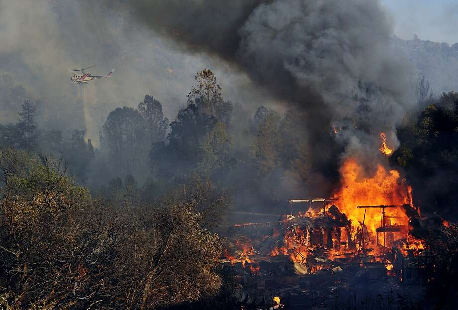 A structure burns along Highway 41 in Oakhurst, Calif., Monday, Aug. 18, 2014. One of several wildfires burning across California prompted the evacuation of hundreds of people in a central California foothill community near Yosemite National Park, authorities said.  Photo: Eric Paul Zamora, Associated Press