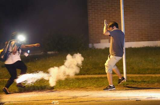 Police lob tear gas at people walking near a protest over the killing of teenager Michael Brown on August 18, 2014 in Ferguson, Missouri. Police shot smoke and tear gas to disperse the protestors with as they became unruly.  Brown was shot and killed by a Ferguson police officer on August 9. Despite the Brown family's continued call for peaceful demonstrations, violent protests have erupted nearly every night in Ferguson since his death. Photo: Scott Olson, Getty Images