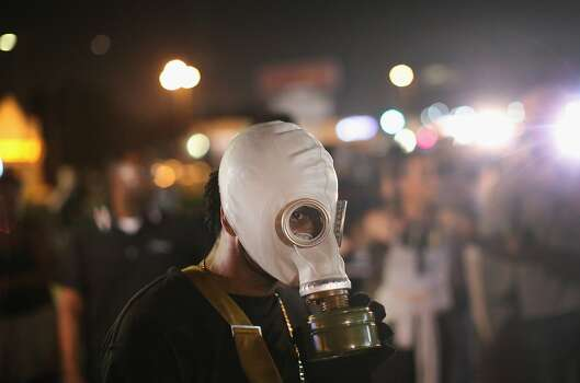 A demonstrator protects himself from tear gas during a protest over the killing of teenager Michael Brown on August 18, 2014 in Ferguson, Missouri. Brown was shot and killed by a Ferguson police officer on August 9. Despite the Brown family's continued call for peaceful demonstrations, violent protests have erupted nearly every night in Ferguson since his death.  Photo: Scott Olson, Getty Images