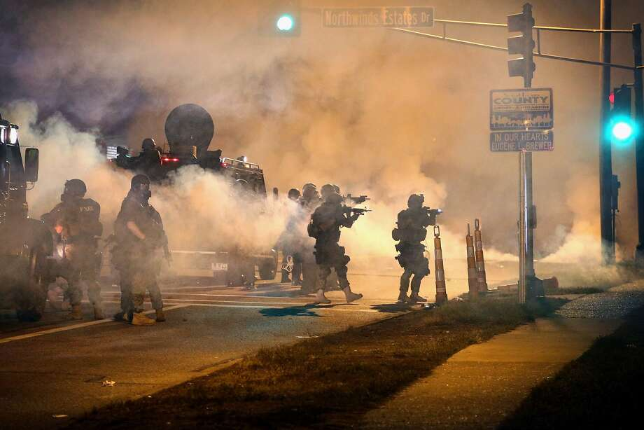 Police attempt to control demonstrators protesting the killing of teenager Michael Brown on August 18, 2014 in Ferguson, Missouri. Police shot smoke and tear gas to disperse the protestors with as they became unruly.  Brown was shot and killed by a Ferguson police officer on August 9. Despite the Brown family's continued call for peaceful demonstrations, violent protests have erupted nearly every night in Ferguson since his death.  Photo: Scott Olson, Getty Images
