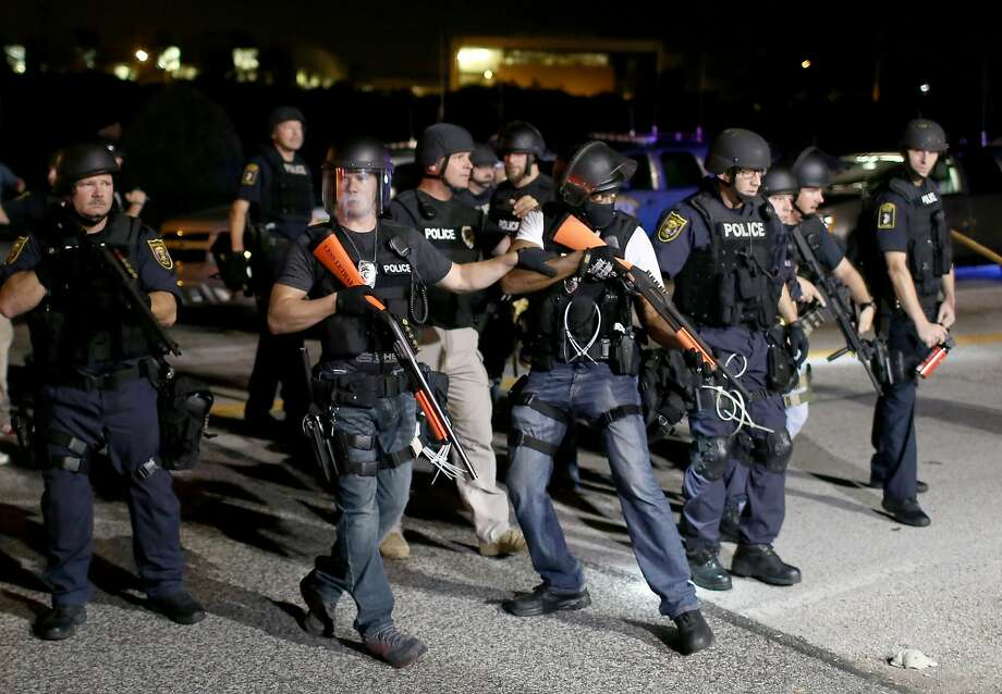 Police officers work to keep order as demonstrators express their feelings on August 18, 2014 in Ferguson, Missouri. Violent outbreaks have taken place in Ferguson since the shooting death of unarmed teenager Michael Brown by a Ferguson police officer on August 9th.  Photo: Joe Raedle, Getty Images
